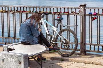 a girl in a jeans jacket sits near a bicycle and listens to music on the phone