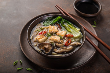 asian vegan noodle soup with tofu cheese, shiitake mushroms and pak choi, dark background