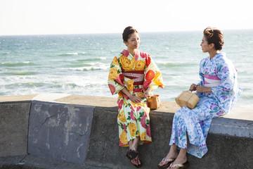 海辺でおしゃべりしている浴衣女性たち