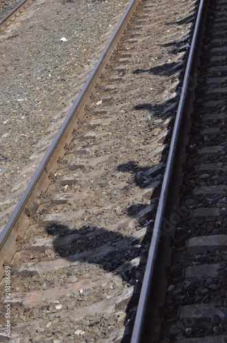 Shiny steel rails lie on the grey gravel on the railroad