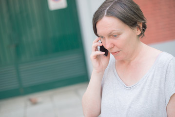 Surprised woman talking on mobile phone out on the street