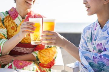 浴衣の女性たちはビールで乾杯している