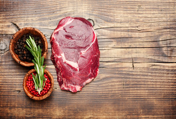 Wall Mural - Ribeye steak with rosemary and peppercorns on a wooden table, top view
