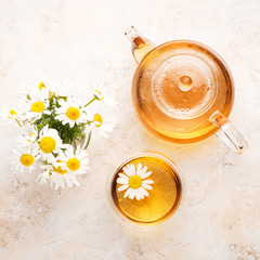 Chamomile herbal tea in a teapot and cup on a beige stone background, top view
