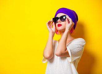 Young girl with pink hair in purple hat and sunglasses on yellow background