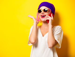 Young girl with pink hair in purple hat talking by mobile phone on yellow background