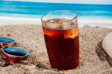 A cold drink in a glass on the beach, a delicious soft drink in the summer