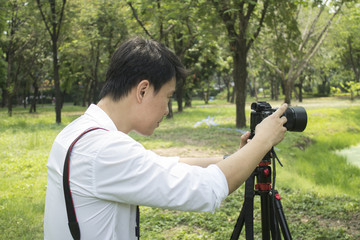 Asian man photographing in the park.  Professional travelling photographer and artist.  Profile view.