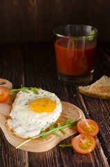 Sandwich with egg, cheese, arugula and tomato juice on a wooden table
