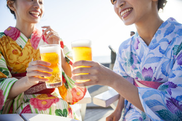 浴衣を着た女性たちは生ビールで乾杯している