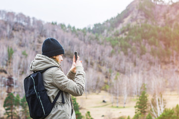 Girl taking photo with phone camera in the mountains