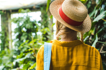 rear view of woman in straw hat surrounded with tropical plants