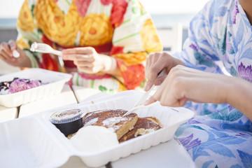 浴衣の女性たちはテラスでパンケーキを食べている