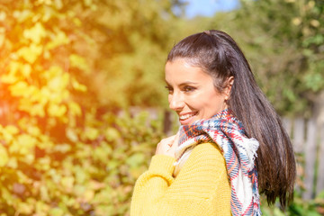 A beautiful woman enjoying the sunlight during Autumn