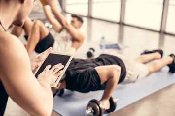 trainer using tablet and counting results of sportsman doing push ups on dumbbells in gym