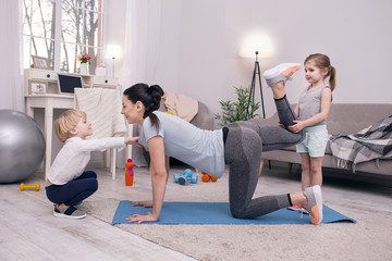 Recreational. Content young mother stretching herself and her kids helping her