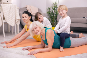 Our leisure. Delighted aged woman sitting on the carpet and exercising with her daughter and grandchildren