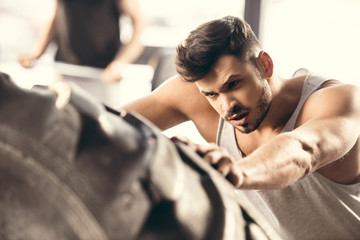 selective focus of athletic young man lifting tyre in gym
