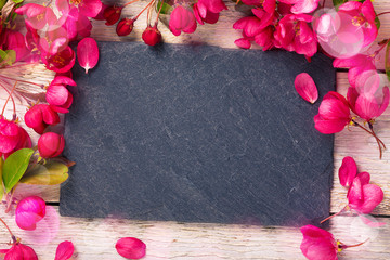 Spring background with slate board and flowers