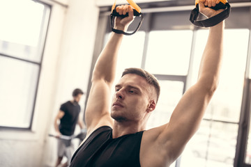 handsome young man training with suspension straps and looking away in gym