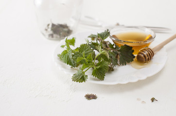 Cut young nettle and bowl of honey on white plate