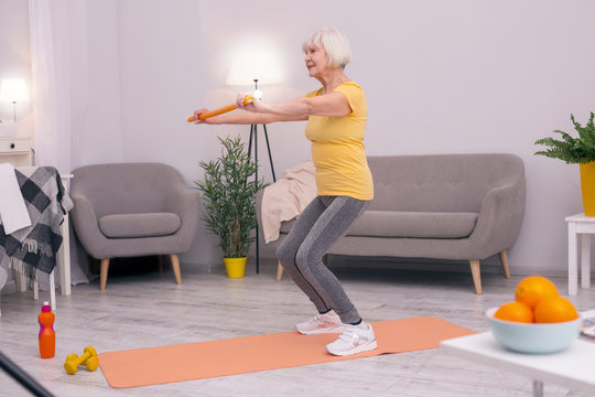 Living healthy life. Athletic elderly woman doing squats in her living room while holding a health wand for correct posture