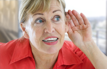 pretty senior woman with hardness of hearing listening