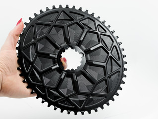 Black oval chainring in woman hand at the white background.
