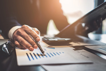 Close up Businessman consultant holding pen and pointing at financial on wooden desk in coffee shop. freelance, tax, accounting, statistics and analytic research concept.