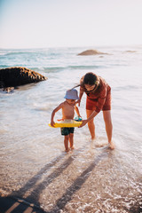 caucasian mother is and son having fun with inflatable ring at beach