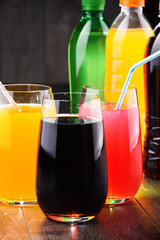 Glasses and bottles of assorted carbonated soft drinks