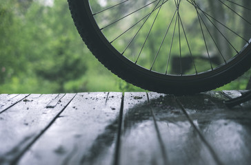Bicycle wheel on the wooden floor under the rain