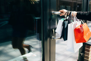 Female hand holding shopping bags and open door of shop