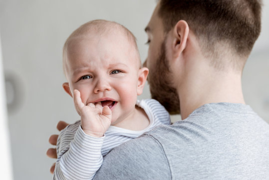 father holding little crying baby boy at home