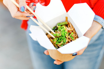 Closeup macro view of a delicious Wok Noodles with greenery in takeout paper box with chop sticks