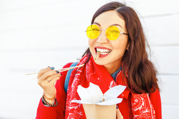 Bright hipster woman eating asian fast food from takeaway box with chop sticks, Wok noodles concept
