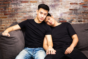 Asian gay couple spending time at home together and looking at camera. Portrait of happy gay men - Homosexual love concept