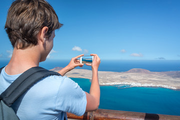 Young man taking pictures with his smartphone, in Lanzarote, Spain