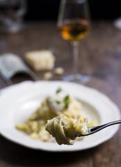 Tenedor con un plato de pasta con queso y vino