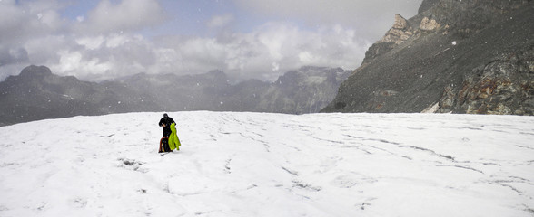 mountain climber gets caught in bad weather and puts on more clothes as he stands on a high alpine glacier with a great panorama view