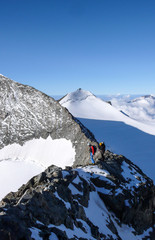 mountain guide and client on a rocky ridge on their way to a high alpine peak with a great view behind them