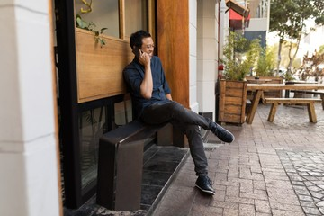 Smiling man talking on smartphone while sitting outside cafe