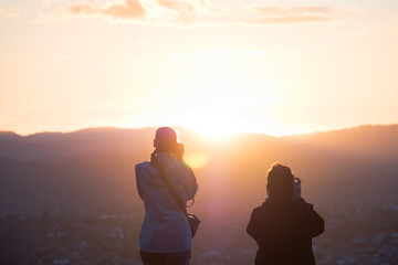 Two women taking a photo together at sunset over the mountain.