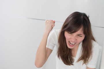 angry woman in toilet by diarrhea, constipation, hemorrhoids, piles; portrait of woman hard pushing in toilet or wc from diarrhea, constipation, food poisoning, hemorrhoids; asian adult woman model
