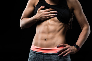 Sporty girl with great abdominal muscles in sportswear on black background