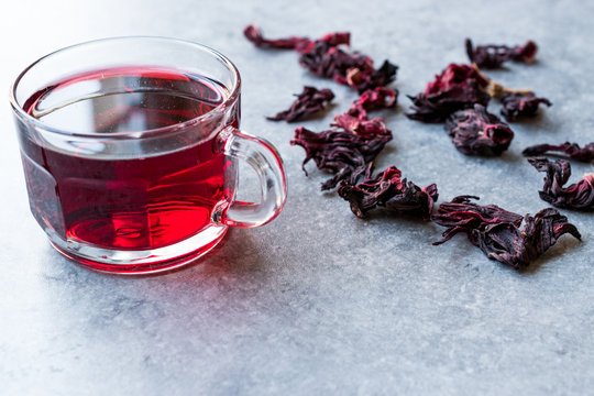 Red Hot Hibiscus Tea in a Glass Mug with Dry Hibiscus Tea Leaves.