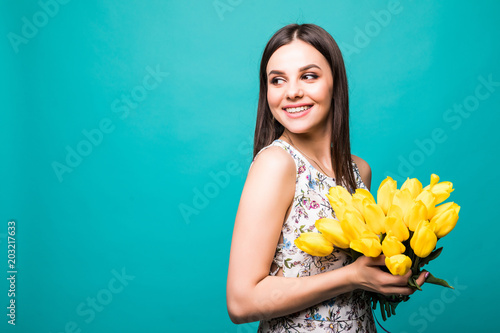 Portrait of a beautiful young woman in ssummer dress holding yellow tulips  bouquet isolated over blue background 44d0cc670