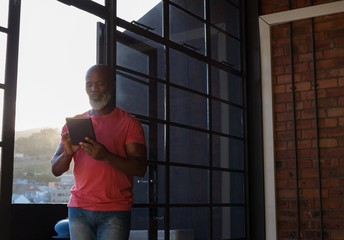Senior man using digital tablet while standing at home
