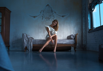 Portrait of a beautiful young woman sitting on a antique Sofa at night.