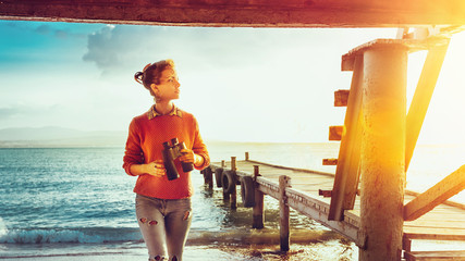 Girl Traveler With Binoculars In Hand Standing By The Sea Near Pier And Enjoying View Of Nature, Front View